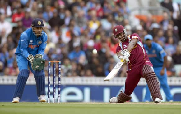 West Indies' Johnson Charles hits a shot beside India's captain and wicketkeeper Mahendra Singh Dhoni during the ICC Champions Trophy group B cricket match between India and West Indies at The Oval cricket ground in London.
