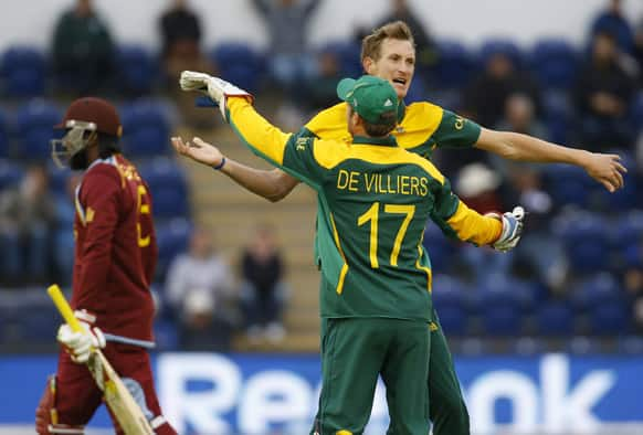 South Africa's Chris Morris and AB de Villiers celebrate taking the wicket of West Indies' Chris Gayle during an ICC Champions Trophy cricket match between West Indies and South Africa at the Cardiff Wales Stadium in Cardiff.
