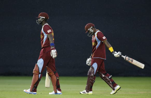 Darren Sammy and Dwayne Bravo are frustrated as they leave the pitch as rain halts play, leaving the match a draw and therefore South Africa go through to the semi-finals, during an ICC Champions Trophy cricket match between West Indies and South Africa at the Cardiff.