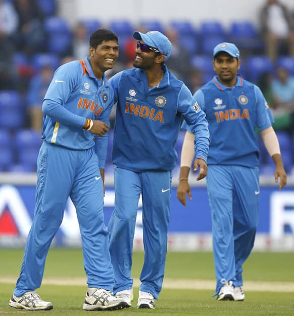 Umesh Yadav, left, and Dinesh Karthik, center, laugh after Yadav is accidentally knocked by the ball during an ICC Champions Trophy semifinal between India and Sri Lanka at the Cardiff Wales Stadium in Cardiff.