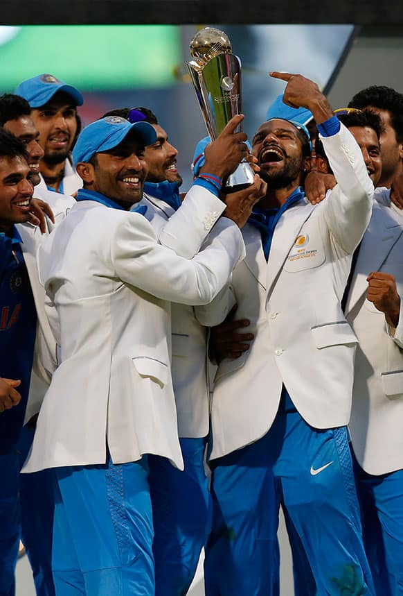 India's players hold up the trophy after their win against England at the end of their ICC Champions Trophy final cricket match at Edgbaston cricket ground in Birmingham.