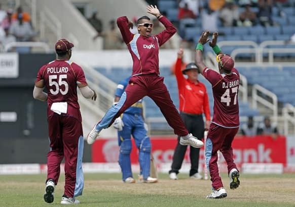 Sunil Narine, jumps to high five with his captain Dwayne Bravo, as teammate Kieron Pollard watches, after taking the wicket of Sri Lanka's opening batsman Mahela Jayawardene for 52 runs during their Tri-Nation Series cricket match in Kingston, Jamaica.