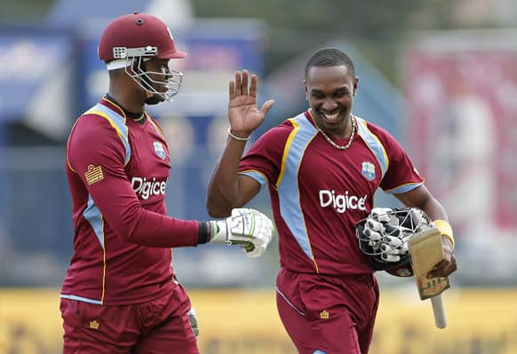 West Indies' captain Dwayne Bravo, right, celebrates with batting partner Marlon Samuels after beating Sri Lanka by 6 wickets with 73 balls remaining during their Tri-Nation Series cricket match in Kingston, Jamaica.