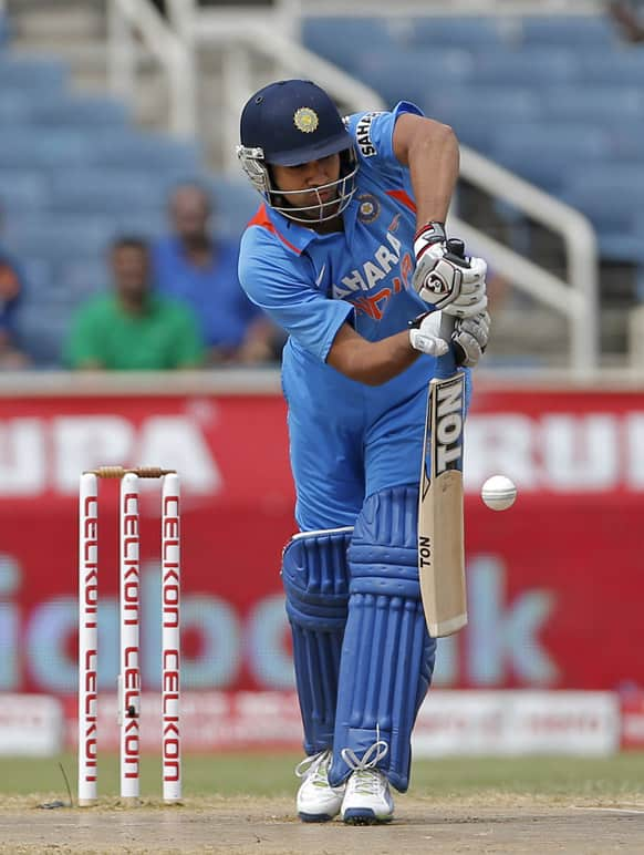 Rohit Sharma drives a delivery off West Indies' Kemar Roach during their Tri-Nation Series cricket match in Kingston, Jamaica.