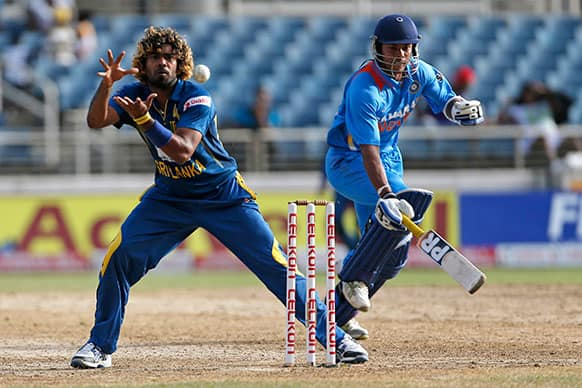 India's Umesh Yadav, right, avoids being run out by Sri Lanka's Lasith Malinga during their Tri-Nation Series cricket match in Kingston, Jamaica.