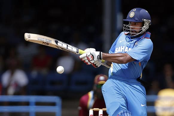 Shikhar Dhawan drives a delivery off West Indies' Kemar Roach during their Tri-Nation Series cricket match in Port-of-Spain, Trinidad.