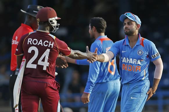 Virat Kohli, right, shakes hands with West Indies' Kemar Roach at the end of their Tri-Nation Series cricket match in Port-of-Spain, Trinidad.
