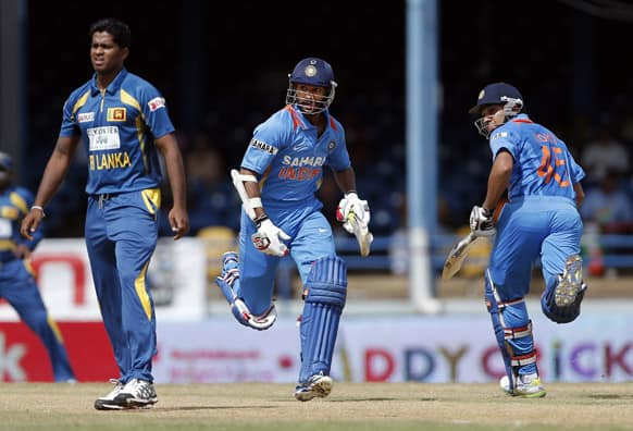 India opening batsmen Shikhar Dhawan, center, and Rohit Sharma, right, run between the wickets as Sri Lanka bowler Dilhara Lokuhettige looks on during their Tri-Nation Series cricket match in Port-of-Spain.