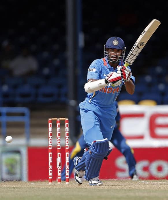 Shikhar Dhawan plays a shot off Sri Lanka bowler Dilhara Lokuhettige during their Tri-Nation Series cricket match in Port-of-Spain, Trinidad.