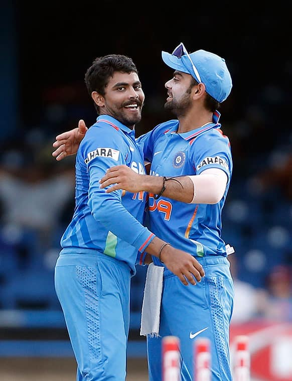 India's Ravindra Jadeja, left, is congratulated by acting captain Virat Kohli for taking the wicket of Sri Lanka's Dinesh Chandimal during their Tri-Nation Series cricket match in Port-of-Spain, Trinidad.