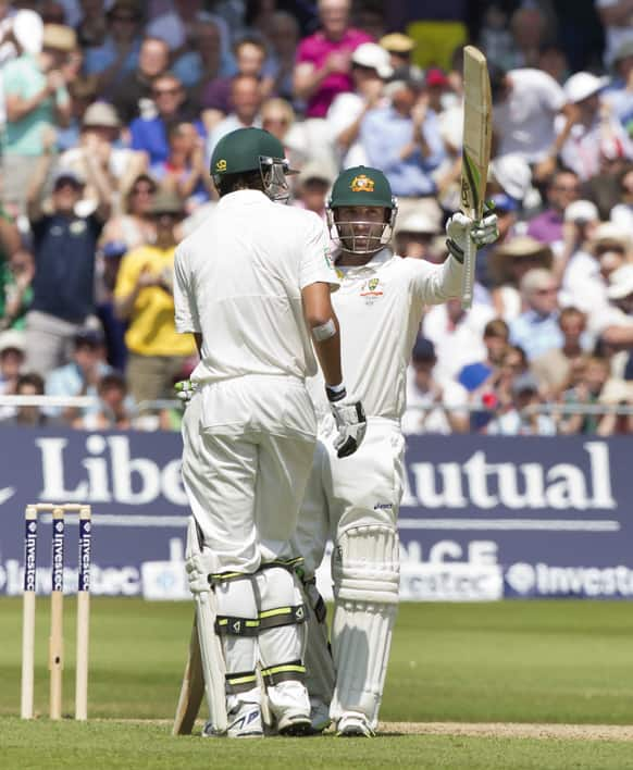 Australia's Phillip Hughes raises hits bat as he reaches a half-century on the second day of the opening Ashes series cricket match against England at Trent Bridge cricket ground, Nottingham, England.