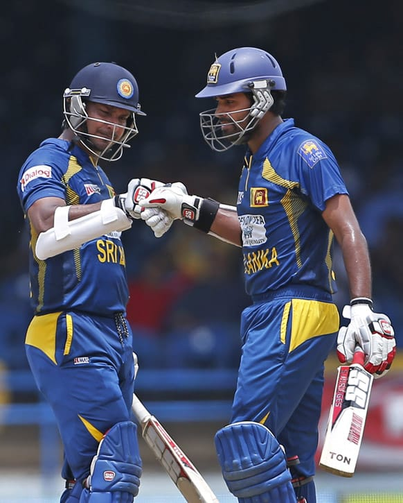 Sri Lanka's Kumar Sangakkara, left, knocks the glove with batting partner Lahiru Thirimanne to congratulate him for hitting a four during the final match against India of the Tri-Nation cricket series in Port-of-Spain.