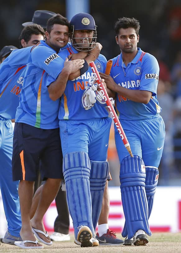 Mahendra Singh Dhoni, center, is hugged by teammates Suresh Raina, left, and Vinay Kumar after their team beat Sri Lanka by one wicke in the final match of the Tri-Nation cricket series in Port-of-Spain, Trinidad.