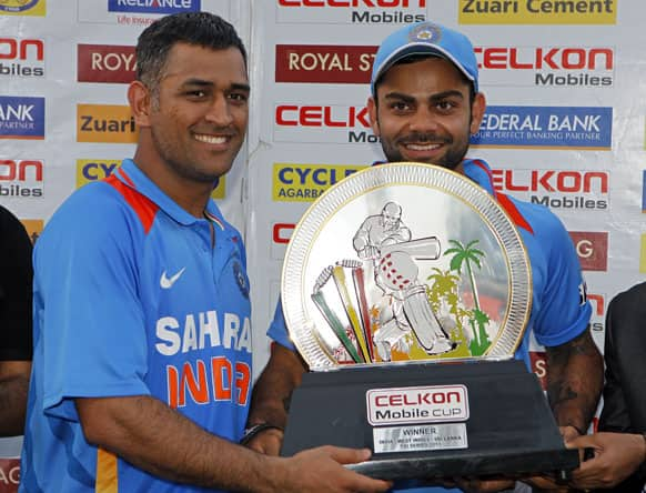 Mahendra Singh Dhoni, left, and teammate Virat Kohli hold the trophy after winning the final match of the Tri-Nation cricket series in Port-of-Spain, Trinidad.