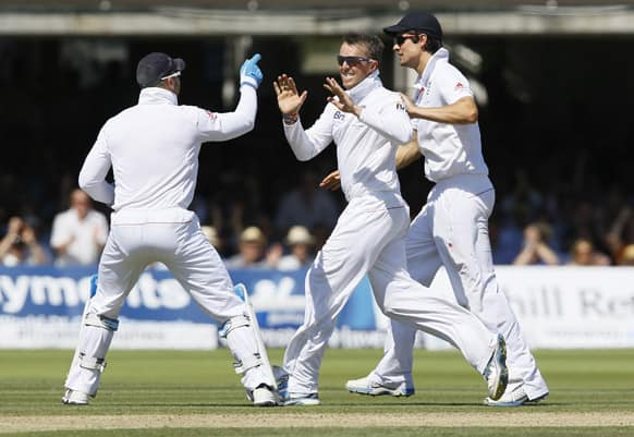 England's Graeme Swann, centre, Alastair Cook, right, and Matt Prior celebrate the wicket of Australia's Steven Smith during day two of the second Ashes Test match held at Lord's cricket ground in London.
