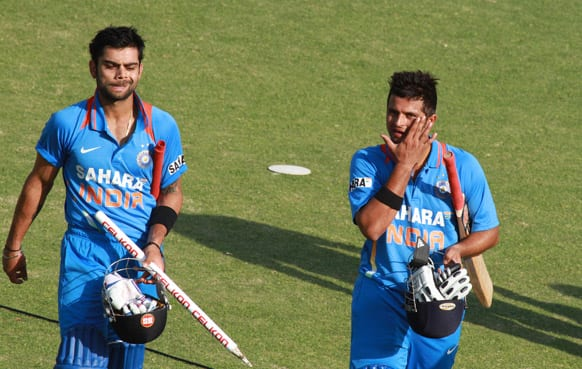 Virati Kohli, left and Suresh Raina walk off the pitch after beating Zimbabwe by 7 wickets during their third one-day international cricket match, in Harare.