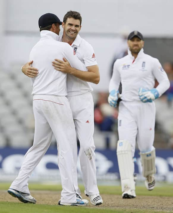 England's James Anderson, centre, embraces Graeme Swann to celebrate the wicket of Australia's Brad Haddin during day four of the third Ashes Test match held at Old Trafford cricket ground in Manchester.