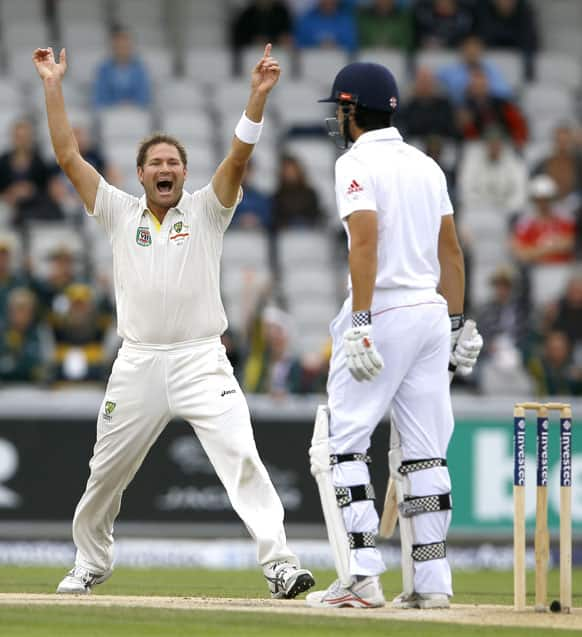 Australia's Ryan Harris, left, celebrates the wicket of England's captain Alastair Cook, right, during day five of the third Ashes Test match held at Old Trafford cricket ground in Manchester, England.