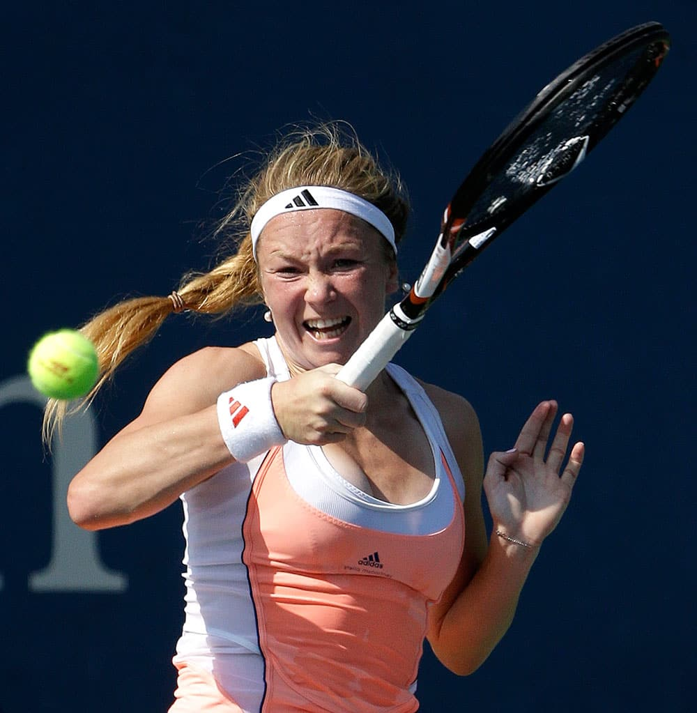 Julia Glushko of Israel returns a shot against Nadia Petrova of Russia during the first round of the 2013 US Open tennis tournament.