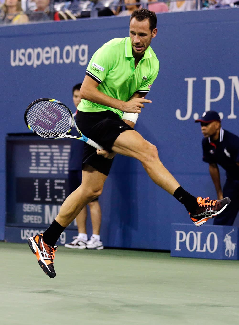 Michael Llodra, of France, follows through on a return between his legs against Andy Murray, of Britain, in the first round of the 2013 US Open tennis tournament.