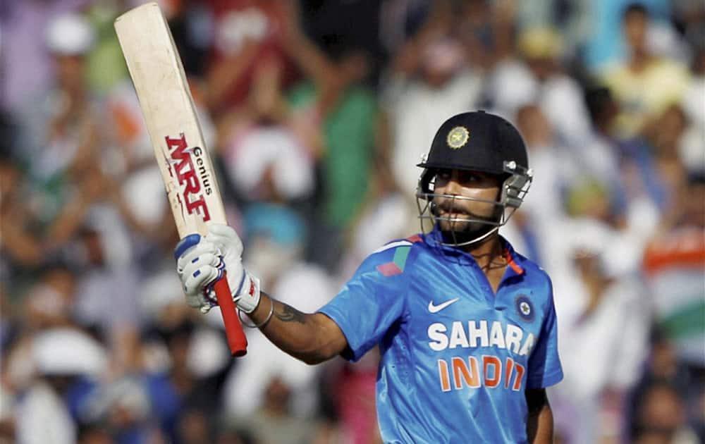 Virat Kohli celebrates his fifty against Australia during the 3rd ODI cricket match at PCA stadium in Mohali.