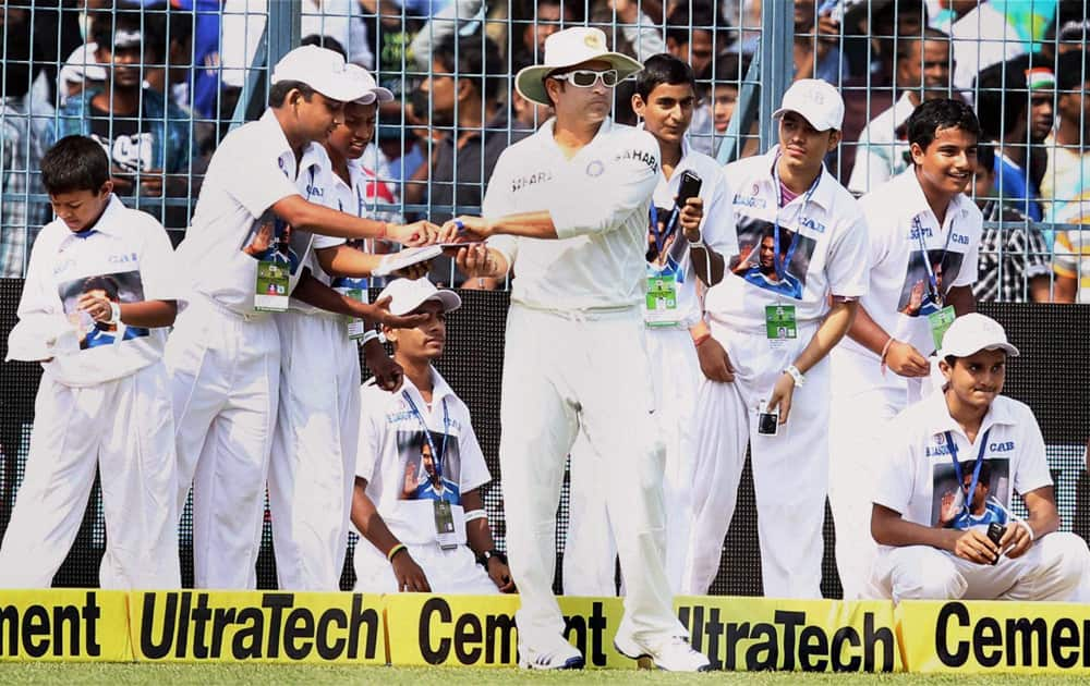 Sachin Tendulkar signs autographs at Eden Garden during the first day of the first test match between India and West Indies in Kolkata.