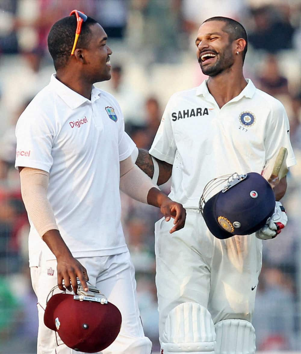 West Indies player D.Bravo shares a light moments with India's opener Shikhar Dhawan (R) at the close of first day of First Test Match at Eden Garden in Kolkata.