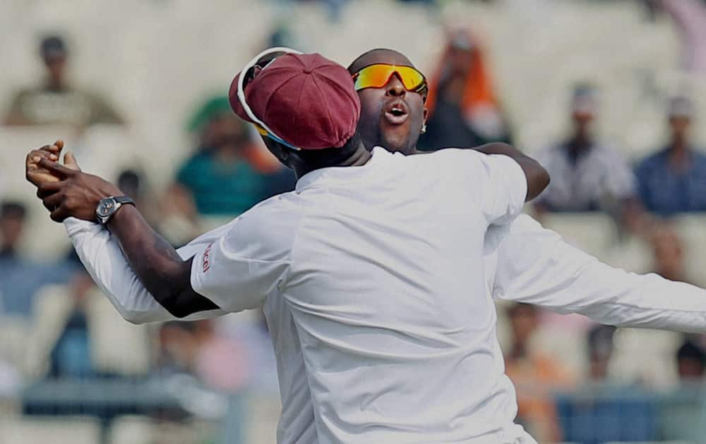 West Indies players Shane Shilingford and Darren Sammy celebrate on the 2nd day of the first test match in Kolkata.