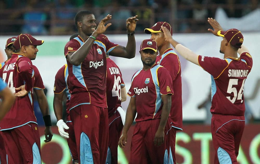 West Indies bowler Jason Holder with team mates celebrates the wicket of Shikhar Dhawan of India during the 1st ODI cricket match in Kochi.
