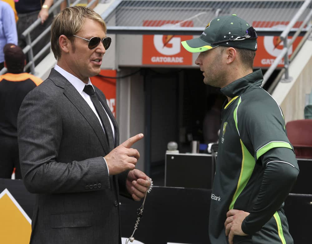 Former Australian cricket player Shane Warne, left, talks to Australian captain Michael Clarke before the start of play on the third day of the series-opening Ashes cricket test between England and Australia at the Gabba in Brisbane.