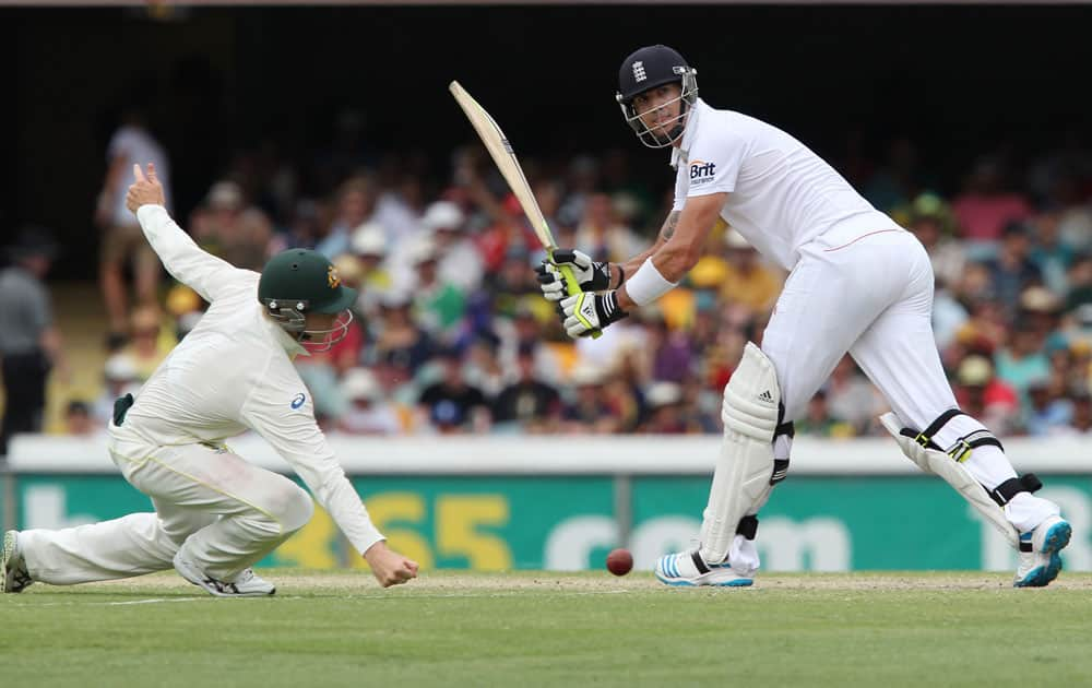 England's Kevin Pietersen, right, plays a shot past Australia's Steven Smith, left, on the fourth day of the series-opening Ashes cricket test between England and Australia at the Gabba in Brisbane.