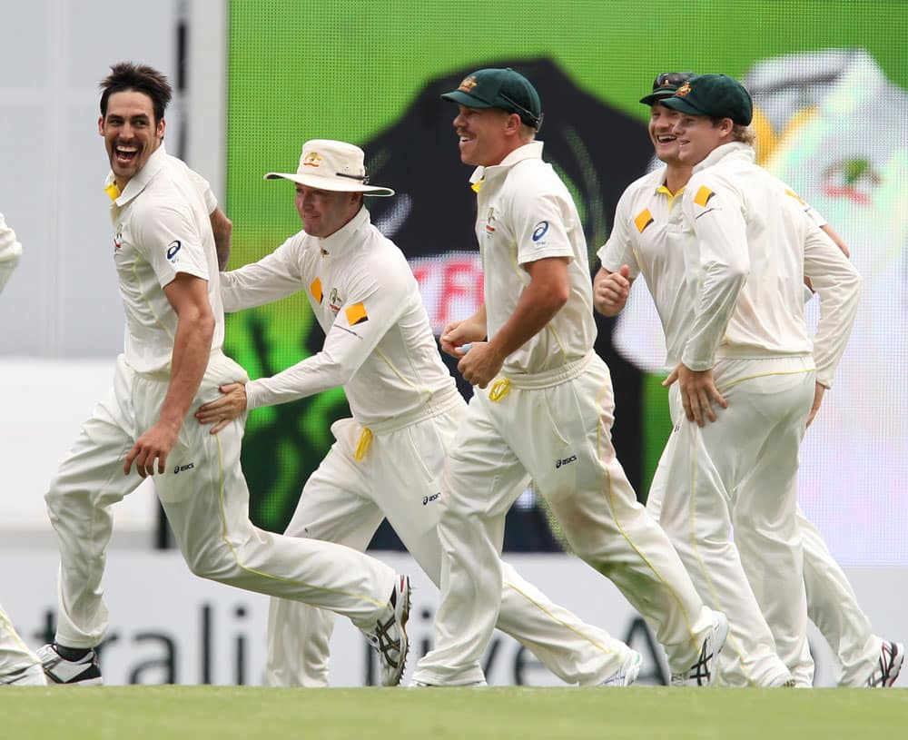 Australia's Mitchell Johnson, Michael Clarke and David Warner, celebrate the wicket of England's Stuart Broad, on the fourth day of the series-opening Ashes cricket test between England and Australia at the Gabba in Brisbane.