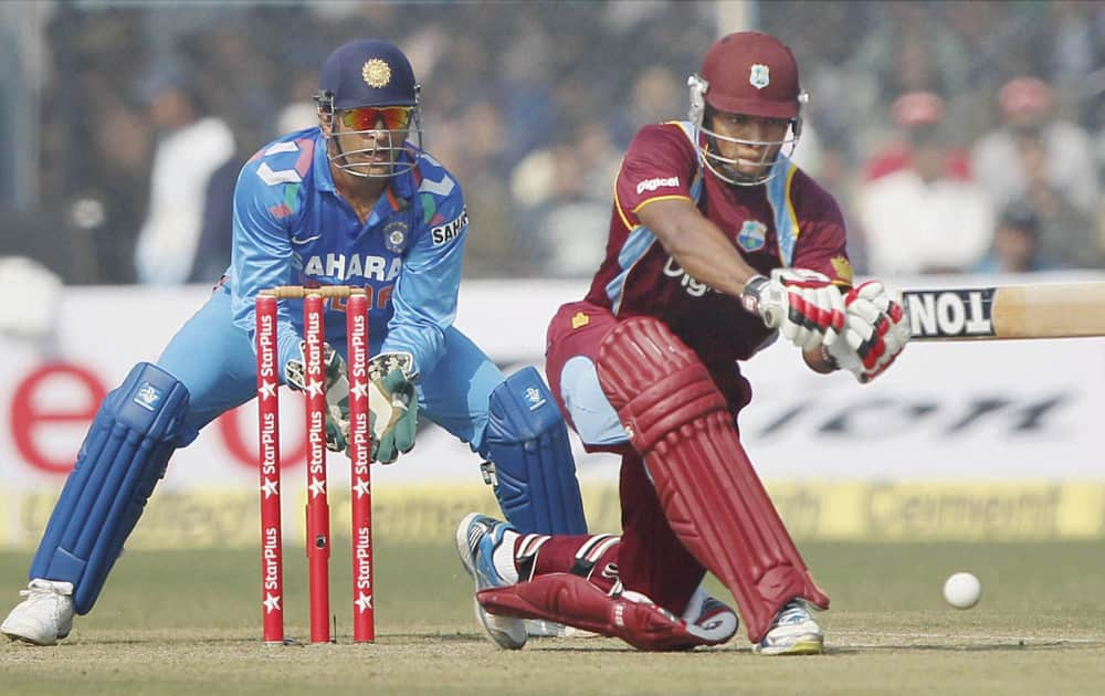M S Dhoni looks on as West Indies batsman KOA Powell plays a shot during their last ODI match at Green Park stadium in Kanpur.