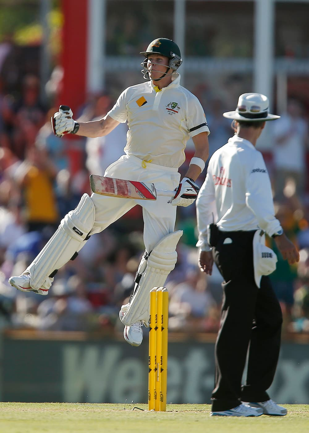 Australia's Steve Smith jumps in the air to celebrate scoring 100 runs against England on the first day of their Ashes cricket test match in Perth, Australia.