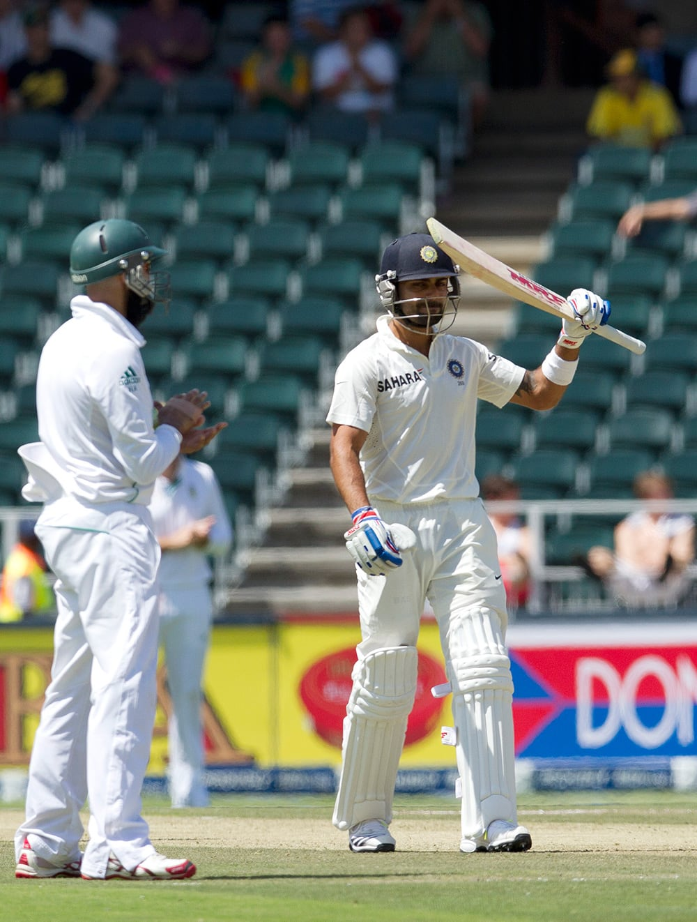 Virat Kohli raises his bat after reaching half century as South Africa's Hashim Amla claps hands during the first day of their cricket test match at Wanderers stadium in Johannesburg, South Africa.