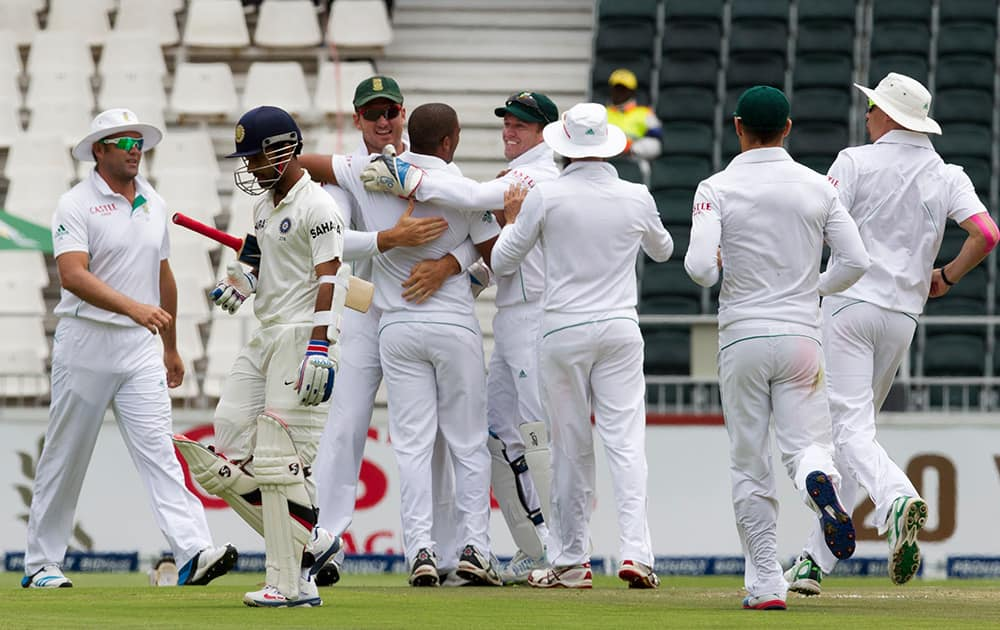 Ajinkya Rahane walks back to the pavilion as South Africa's bowler Vernon Philander celebrates his dismissal with teammates during the second day of their cricket test match at Wanderers stadium in Johannesburg, South Africa.
