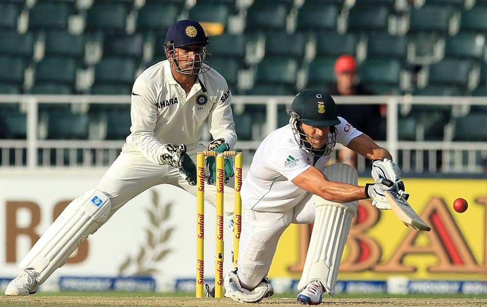 Francois du Plessis, plays a shot as India's captain Mahendra Singh Dhoni during the second day of their cricket test match at Wanderers stadium in Johannesburg, South Africa.