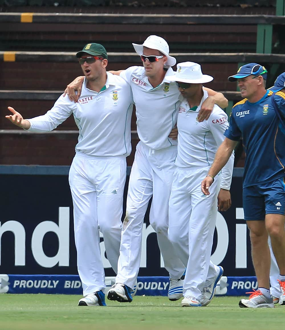 Graeme Smith with Alviro Petersen assist teammate Morne Morkel, after hurting his right ankle during India's 2nd innings on the third day of their cricket test match at Wanderers stadium in Johannesburg, South Africa.