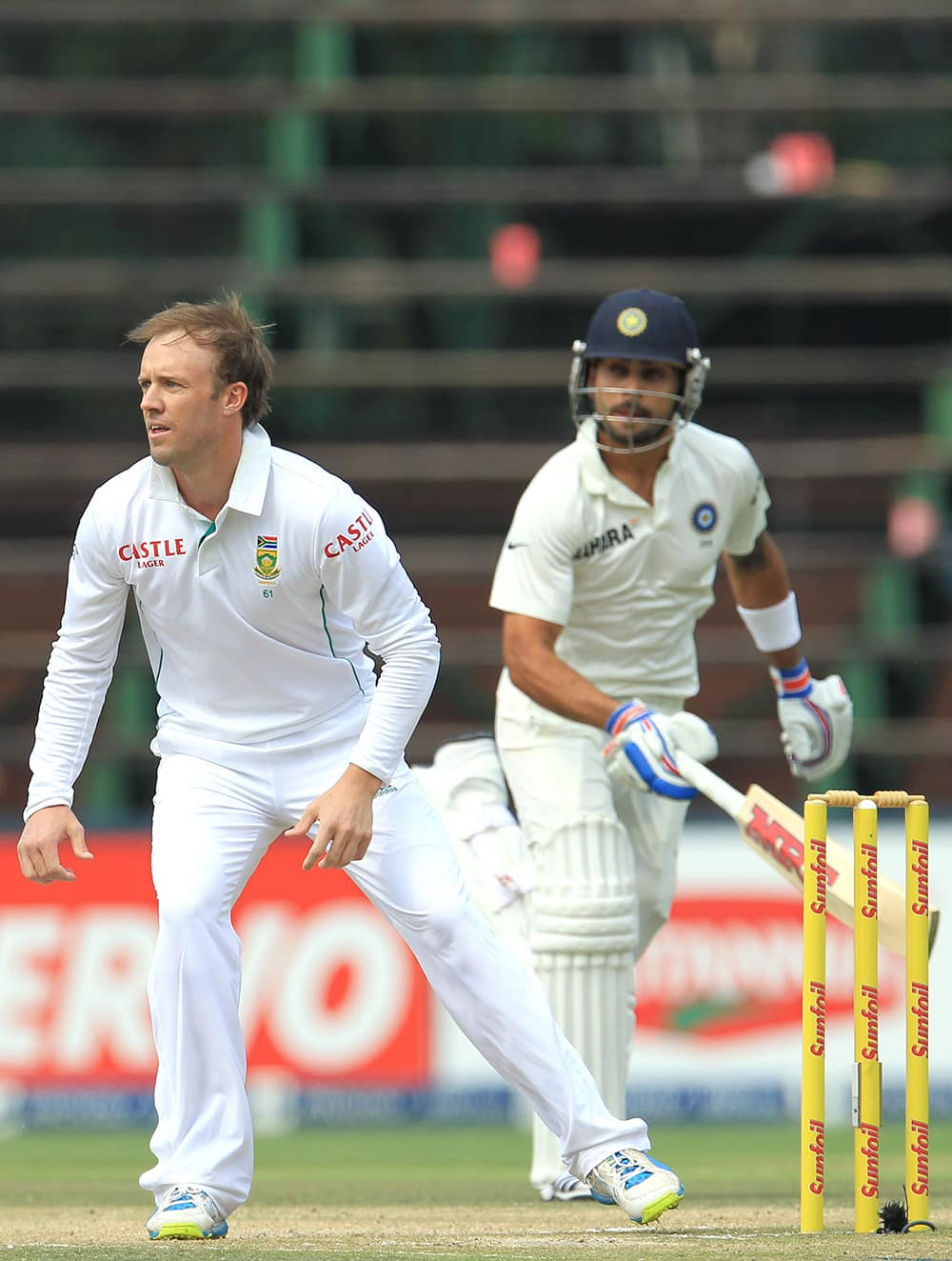 Ab de Villiers awaits the ball as Virat Kohli makes a run during India's 2nd innings on the third day of their cricket test match at Wanderers stadium in Johannesburg, South Africa.