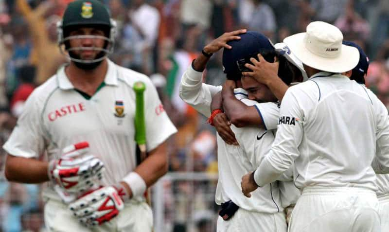 South African cricketer Jacques Kallis, walks back to the pavilion, as Indian cricketers celebrate his dismissal during the fourth day of the second test cricket match in Calcutta.