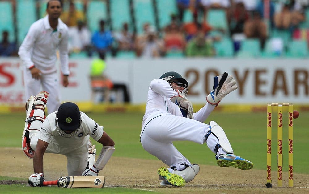 South Africa's wicketkeeper Abraham Benjamin de Villiers, right, attempts a run out against India's batsman Cheteshwar Pujara, left, during first day of their cricket test match at Kingsmead stadium, Durban, South Africa.