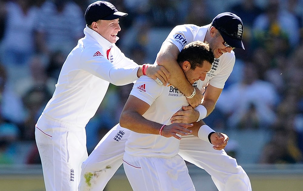 England Tim Bresnan celebrates with teammates James Anderson and Joe Root after taking the wicket of Australia's Mitchell Johnson for 2 runs during their Ashes cricket test match at the Melbourne Cricket Ground in Melbourne, Australia.