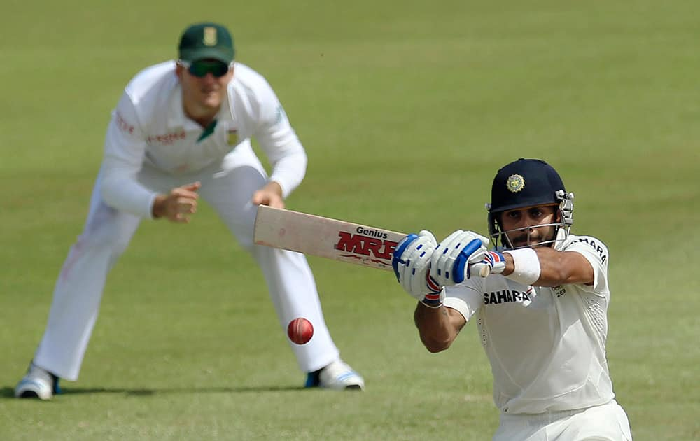Virat Kohli plays a shot as Graeme Smith watches during second day of their cricket test match at Kingsmead stadium, Durban, South Africa.