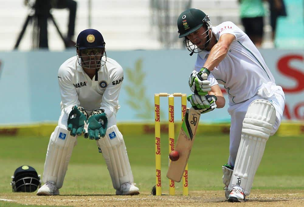 South Africa's batsman Abraham Benjamin de Villiers, right, plays a shot as India's captain Mahendra Singh Dhoni, left, watches, on the third day of their cricket test match at Kingsmead stadium, Durban, South Africa.