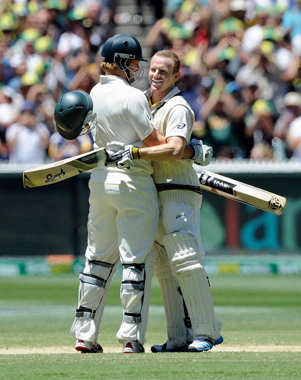 Australia's Shane Watson, left, congratulates Chris Rogers on making 100 runs against England during their Ashes cricket test match.