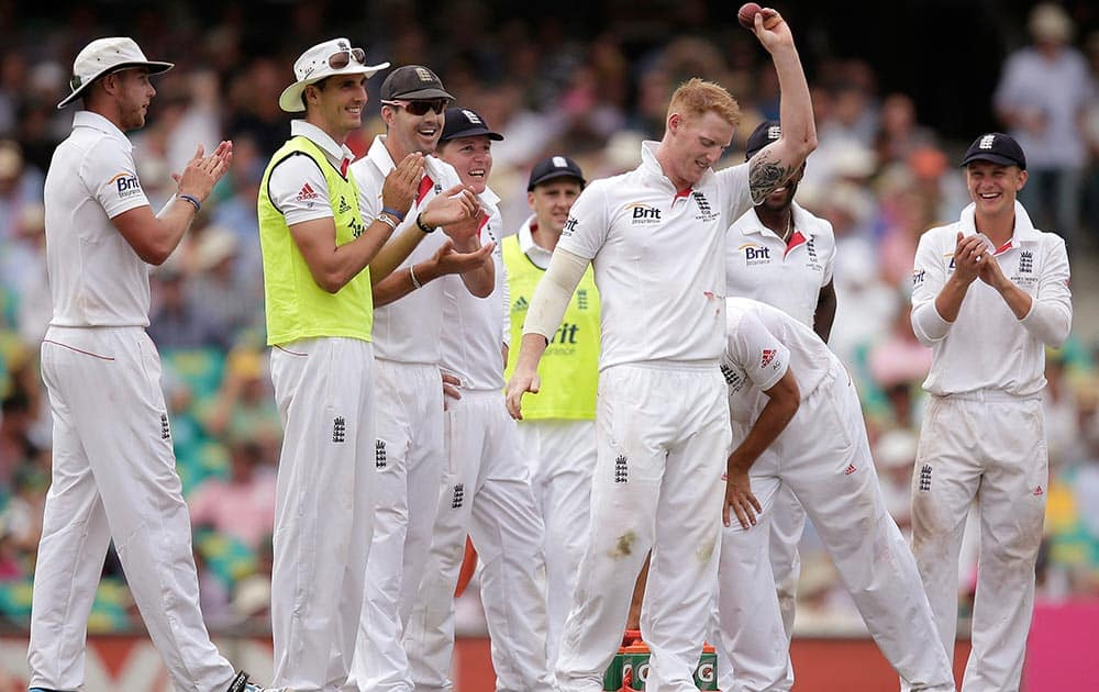 England's Ben Stokes, third right, holds up the ball after taking 5 wickets against Australia in their Ashes cricket test match at the Sydney Cricket Ground in Sydney.