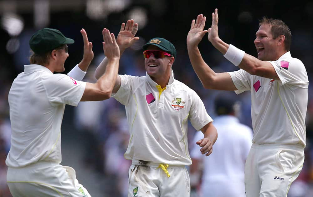 Australia's Shane Watson, left, David Warner, center, and Ryan Harris, right, celebrate after taking the wicket of England's Kevin Pietersen for 3 runs during their Ashes cricket test match at the Sydney Cricket Ground in Sydney.