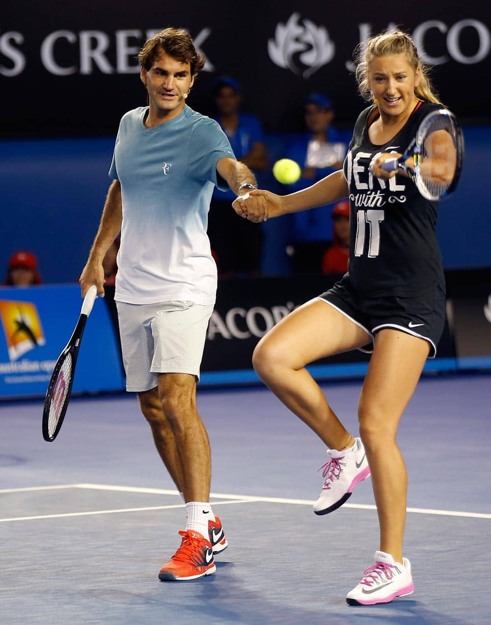 Victoria Azarenka of Belarus plays a shot as she holds hands with Switzerland's Roger Federer during an exhibition match on Kids Tennis Day ahead of the Australian Open tennis championship in Melbourne.