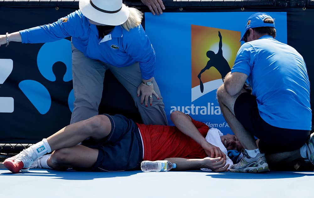 Frank Dancevic of Canada lies on the court after collapsing during his first round match against Benoit Paire of France as temperatures topped at 43 C (108 F) at the Australian Open tennis championship in Melbourne, Australia.