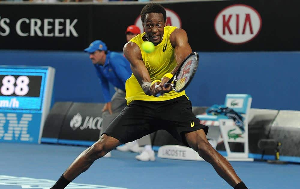Gael Monfils of France makes a backhand return to Ryan Harrison of the U.S. during their first round match at the Australian Open tennis championship in Melbourne, Australia.